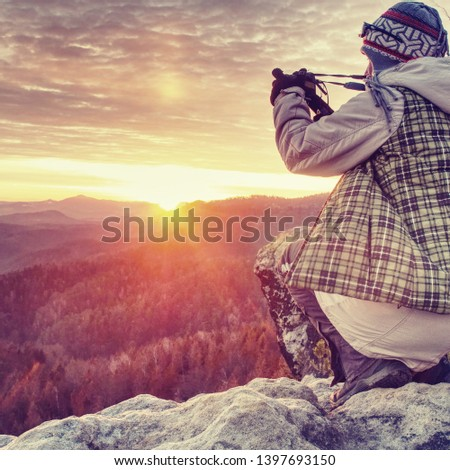 Photographer taking picture. Woman artist photo enthusiast stay with camera above valley and works. Nice view over dried trees in valley.