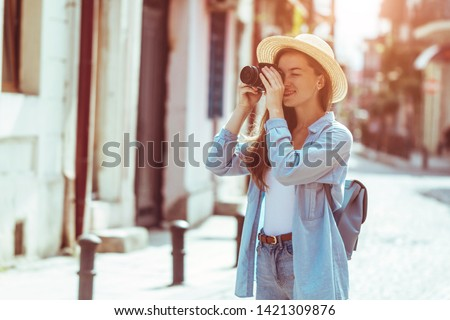 Photographer traveler in hat takes pictures of sights while walking along the street of a european city. Vacation and travel holidays. Traveling lifestyle
