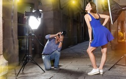 Photographer using professional camera and light equipment for taking pictures of adult woman in blue dress on town street