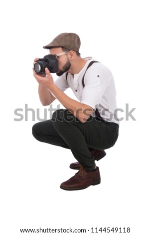 Photographer wearing a classic outfit, holding his camera and taking a photo, sitting on the floor, isolated on white background
