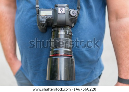 photographer with a camera hanging on his neck. full frame camera on photographer. street photographer. paparazzi.
