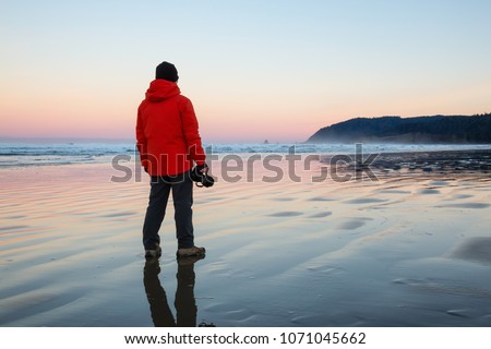 Photographer with a camera is standing on the sandy beach during a vibrant and colorful winter sunrise. Taken in Canon Beach, Oregon Coast, United States of America.