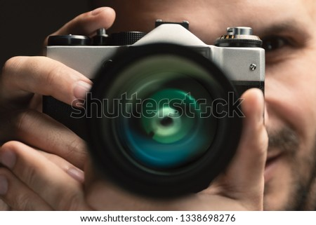Photographer with an old vintage film camera. Focus on camera body. #1338698276