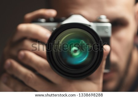 Photographer with an old vintage film camera. Focus on the lens. #1338698288