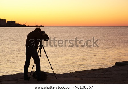 Photographer with camera and tripod take a picture at sunset
