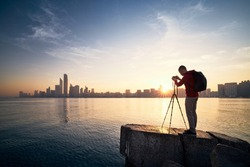 Photographer with camera on tripod photographing urban skyline at sunrise. Abu Dhabi, United Arab Emirates.