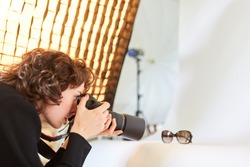 Photographer with camera photographs a pair of glasses for product photography