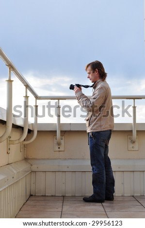 photographer with camera standing on the roof, taking pictures