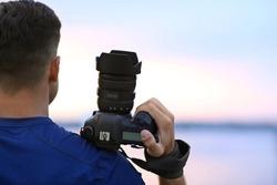 Photographer with professional camera near river at sunset, closeup
