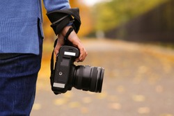 Photographer with professional camera outdoors on autumn day, closeup