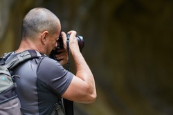 Photographer with professional camera taking pictures outdoor