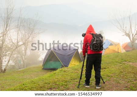Photographer with tripod and camera taking photographs of foggy mountain.