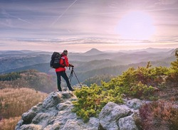 Photographer with tripod in hand. Man hold tripod, stand on rock. Hiker admiring the stunning misty mountain range, sunny morning. Epic travel in a wilderness,