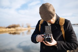 Photographer with vintage photo camera. Bearded man using retro camera outdoor