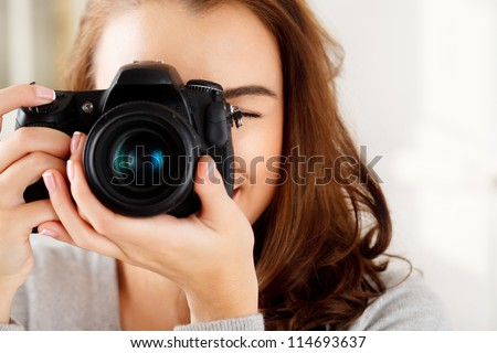 Photographer woman girl is holding dslr camera taking photographs