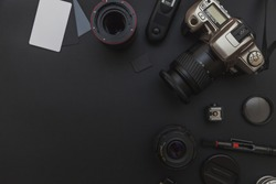 Photographer work place with dslr camera system, camera cleaning kit, lens and camera accessory on dark black table background. Hobby travel photography concept. Flat lay top view copy space