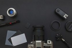 Photographer work place work space with dslr camera system, camera cleaning kit, lens and camera accessory on dark black background. Hobby travel photography concept. Flat lay top view copy space
