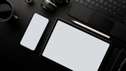 Photographer work table concept, blank screen tablet and smartphone mockup with film camera, laptop, coffee on black background