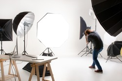 Photographer working in modern lighting studio with many kinds of flash and accessories, taking to empty area in look like shot to someone. Idea for adding people or object to photo.