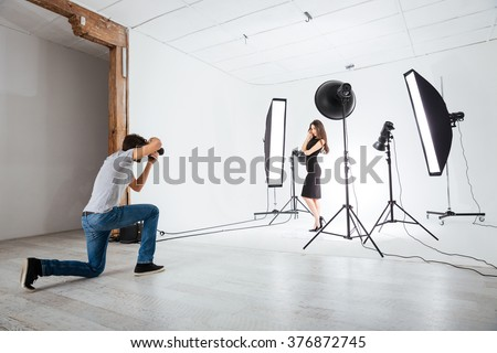 Photographer working with model in studio with equipments