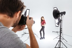 Photographer working with model in studio with softboxes