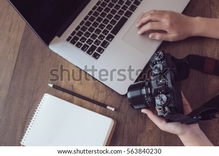 Photographer workplace, Camera,Laptop,Memo on wooden desk. #563840230