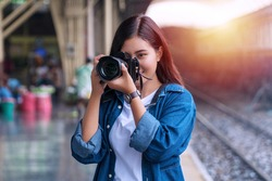 Photographer young woman taking pictures holding digital camera while standing in the train station.Attractive smile girl traveler using  camera in her hand taking photo in train station with sunlight