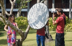 Photographers assistant holding reflector helping to control light over model at location shoot at tropical garden location