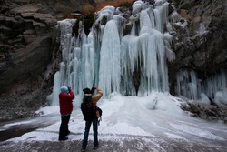 Photographers in red jackets in front of a high altitude frozen water falls in Leh in India