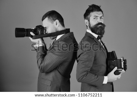 photographers working. Men with beards hold photo cameras on blue background. Business or promotion concept. Reporters in classic suits work on event.