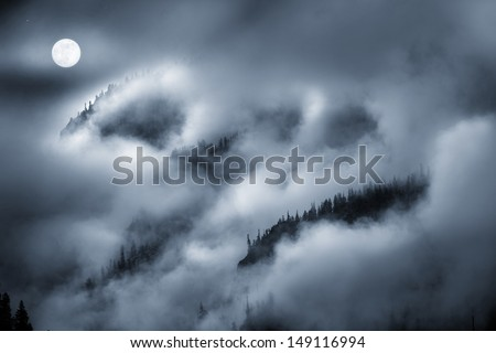Photographic illustration of a night time Fog Covered Mountain lit by bright Full Moon. Makes for a spooky background for Halloween illustration or a moody nature theme.
