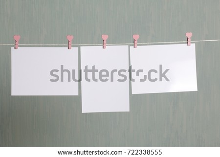 Photographic prints hang after developing on a cord and dry. There is a place to insert your content. Attached to the cord with clothes pegs in different positions. On a gray-green background.