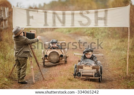 Photographing end of the competition between the two boys racers on homemade wooden car. Retouch for retro