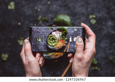 Photographing food. Hands taking picture of delicious vegetable salad with smartphone