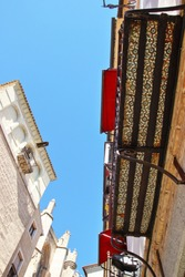 Photographs in angle against chopped streets and facades of Toledo, Spain, narrow street, , art, with decorative tiles under the balconies,  in the background the cathedral,