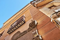 Photographs in angle against chopped streets and facades of Toledo, Spain, narrow street, windows and balconies with wrought iron grills, art, with decorative tiles under the balconies,