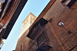 Photographs in angle against chopped streets and facades of Toledo, Spain, narrow street, windows and balconies with wrought iron grills, art, lamppost, with tower of church,