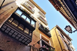 Photographs in angle against chopped streets and facades of Toledo, Spain, narrow street, windows and balconies with wrought iron grills, art, with decorative tiles under the balconies,lamppost,