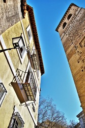 Photographs in angle against chopped streets and facades of Toledo, Spain, narrow street, windows and balconies with wrought iron grills, art, lamppost, with  with Bell tower of Santa Leocadia church,