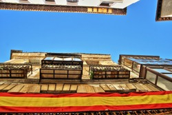 Photographs in angle against chopped streets and facades of Toledo, Spain, narrow street,with decorative tiles under the balconies, balconies with the Spanish national flag,