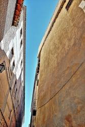 Photographs in angle against chopped streets and facades of Toledo, Spain, very narrow and very high streets, windows and balconies with wrought iron grills, art,