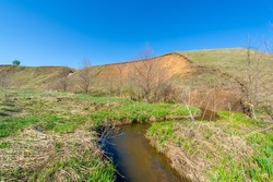 Photographs of a landscape, stream, Gully is a relief created by running water, which rapidly collapses into the soil, usually on a hillside. Gullies resemble large ditches or small valleys,