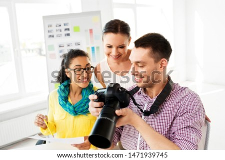 photography and creative people concept - photographers with camera at photo studio