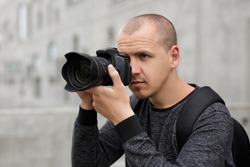 photography and tourism concept - handsome male photographer taking photo with modern dslr camera over concrete building background