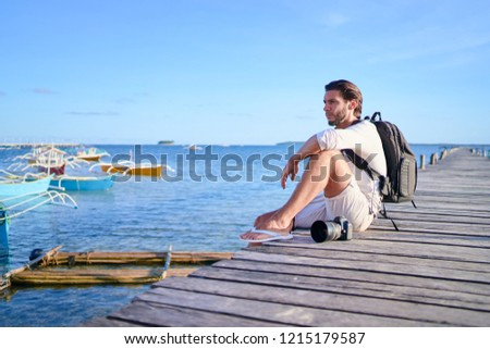 Photography and travel. Young man with rucksack holding camera sitting on wooden fishing pier with beautiful tropical sea view.