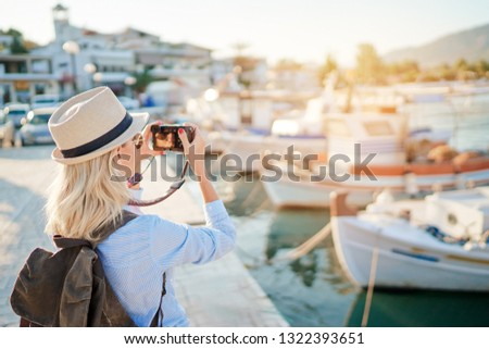 Photography and travel. Young woman with rucksack holding camera sitting on wharf with beautiful sea view with fishing boats.