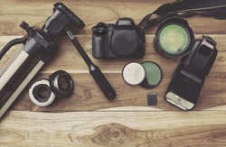 photography equipment, camera, tripod,flash and computer on wood table