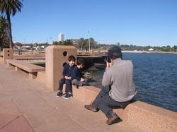 Photography. Father photographer takes photos of his children on the waterfront of the city. Kids being photographed with the ocean in the background and illuminated by the sun.