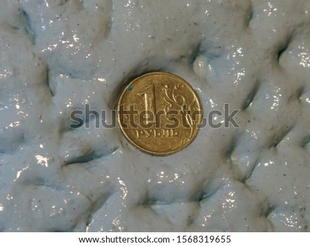 Photography of a ruble coin drowning in a blue slime. Concepts of instability and financial failure