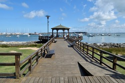 Photography of a wooden pier and a gazebo and the boats anchored at  the port of Punta del Este City, Uruguay